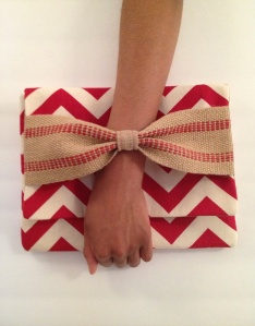 Clutch with bow features a hand thru detail.